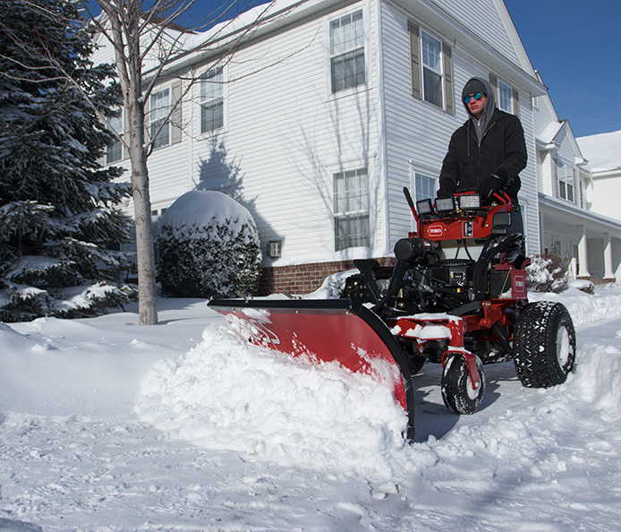 Toro Multi Force stand on mower plowing snow