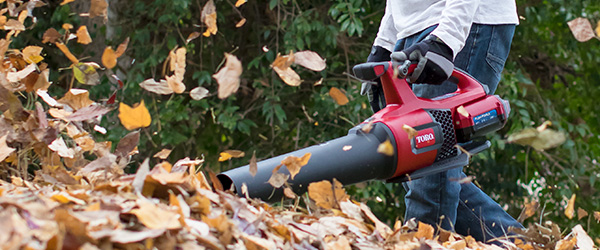 image shows a man leaf blowing a pile of leaves with a 60V battery leaf blower